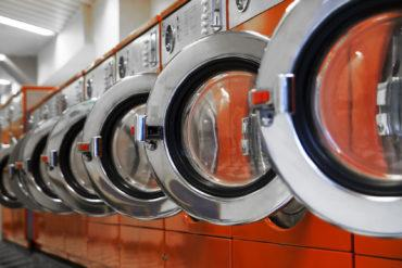 Row of washing machines in laundromat © PiXXart Photography - Fotolia.com