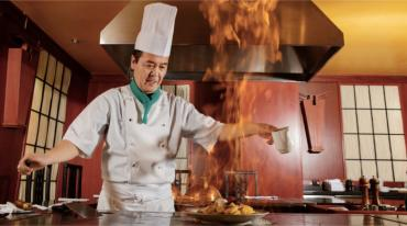 Chef in kitchen with flaming pan © Viacheslav Iakobchuk - Fotolia.com