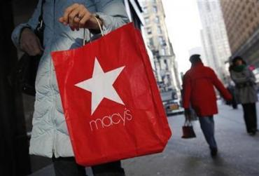 A woman holds a Macy's Inc shopping bag outside a store in New York