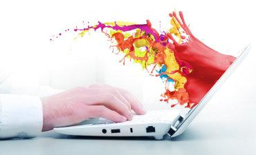 Rainbow colors surging out of laptop © Sergey Nivens - Fotolia.com