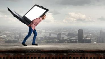 Young man carrying big laptop on back against cityscape © Sergey Nivens - Fotolia.com