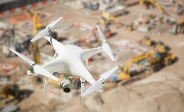 Quadcopter drone flies over heavy equipment at construction site © Andy Dean - Fotolia.com