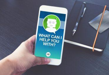 Hand holding mobile showing AI chatbot customer service agent on screen. © weedezign - Fotolia.com
