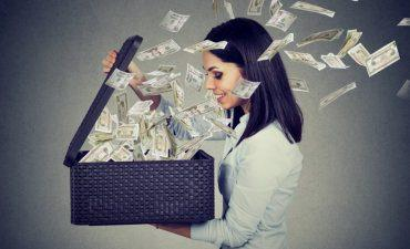 Happy woman opening box with money flying away © pathdoc - Fotolia.com