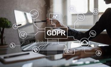 GDPR graphic over person at desk with laptop © Wright Studio - Shutterstock