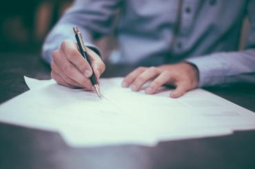 Image of someone signing a contract