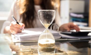 Close-up of hourglass in front of business woman at work © Andrey_Popov - shutterstock