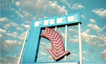 Vintage neon arrow sign showing free against blue cloud sky © J.D.S - shutterstock