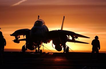 An image of a military person and a fighter jet at sunset