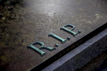 Image of a tombstone with the letters 'RIP' on it