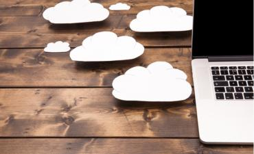 Laptop close up with white clouds on table - cloud migration concept © Simon Bratt - shutterstock