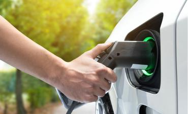 Hand holds charging cable plugged into electric car (EV) © Zapp2Photo - shutterstock