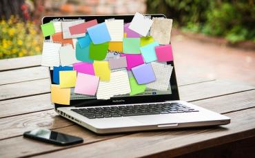Image of a laptop covered in finance post it notes