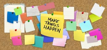 Image of post-it notes on a board with the words 'make things happen'