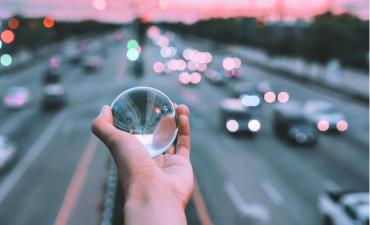 Glass ball in hand above busy freeway blur © Kan bokeh - shutterstock