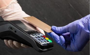 Contactless POS hands wearing gloves against COVID-19 © Lili Topa - shutterstock