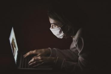 Image of someone wearing a mask at a laptop during COVID-19 pandemic