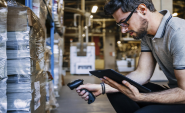 Man scanning boxes while holding tablet © ServiceNow