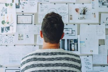 Image of someone looking at a whiteboard filled with plans and ideas
