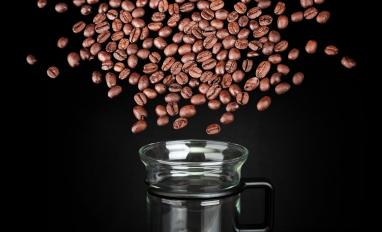 Blast cloud of coffee beans over mug made of glass on black background