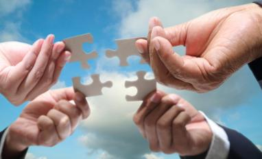 Business team hands joining jigsaw pieces in cloudy blue sky © hin255 - Fotolia.com