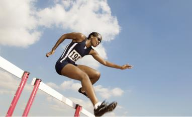 Low angle view of female athlete jumping hurdle © sirtravelalot - shutterstock