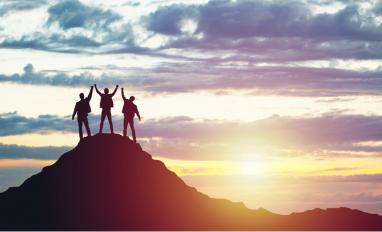 Three people silhoutted by sun celebrate success on mountain top © Evdokimov Maxim - shutterstock