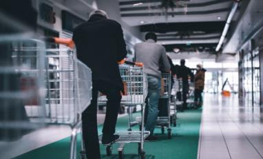 Man standing in queue with shopping cart © Adrien Delforge - Unsplash
