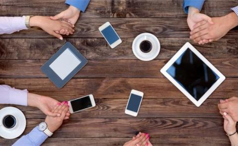 usiness team in handclasp unity with mobile devices at vintage table © alexbrylovhk - Fotolia.com