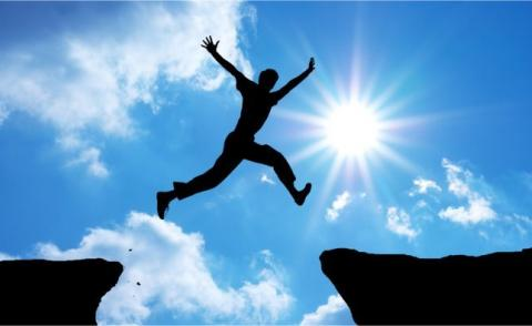 Man leaping across gap in rocks against sunburst on blue sky © GIS - Fotolia.com