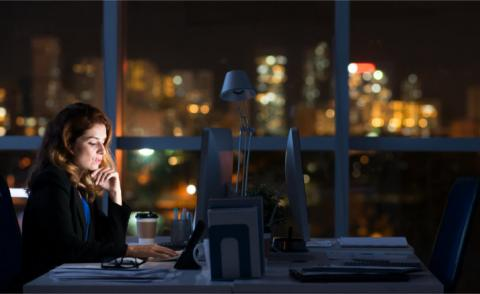 Business woman working at computer in dark office © DragonImages - Fotolia.com