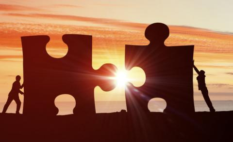 Figures silhouetted by sun push jigsaw pieces together © Sergey Nivens - Fotolia.com