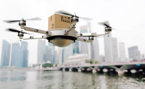 Drone carries fragile parcel over water near city © tiero - Fotolia.com