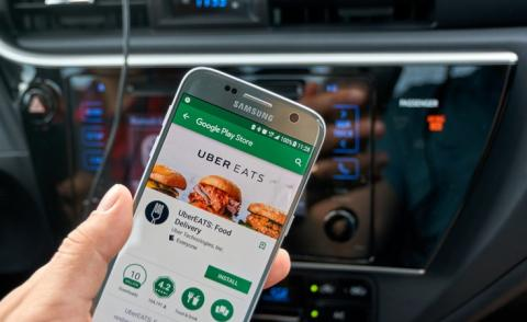 Driver looks up Uber Eats application on Samsung S7 © dennizn - shutterstock