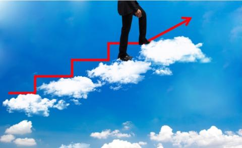 Businessman walking up cloud stairs with red growth arrow on blue sky © Photomontage - shutterstock
