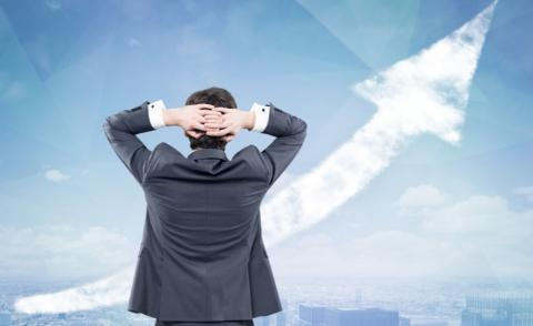 Rear view of businessman hands behind head looking at cloudy arrow in city sky © ImageFlow - shutterstock
