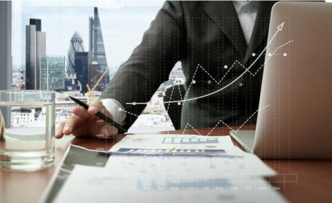 Business person working on financial analysis with city behind © everything possible - shutterstock