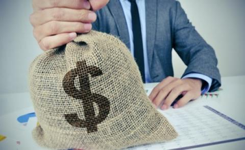 Business man at desk holds large burlap money bag with US dollar sign © nito - shutterstock