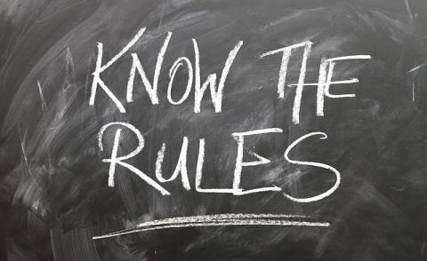 Image of a chalk board with writing on that says 'Know the Rules'