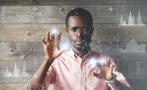 Data scientist in glasses and pink shirt through touchscreen display, with wood background © WAYHOME studio - shutterstock