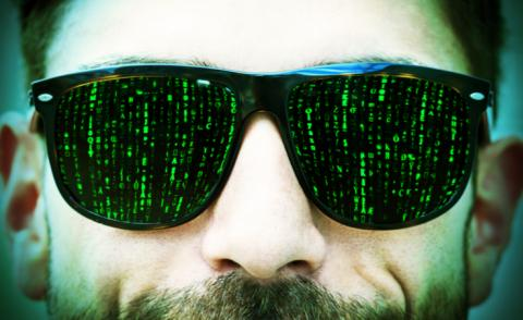 Matrix-style green code on dark glasses worn by hipster man © Juergen Faelchle - shutterstock