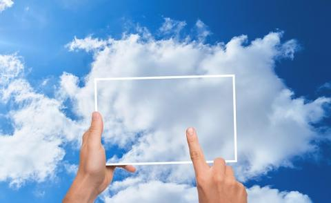 Image of an tablet being used against a cloud backdrop
