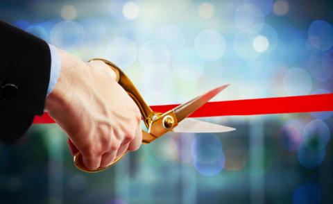 Businessman cutting red ribbon with pair of scissors close up © Africa Studio - shutterstock
