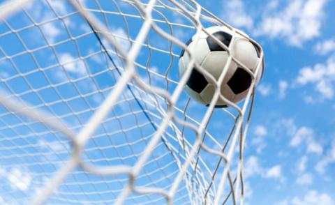 Soccer ball hits goal net with cloud and sky behind © Billion Photos - shutterstock