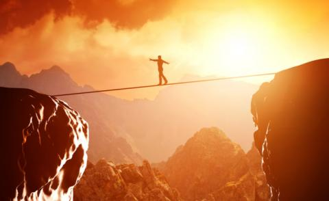 Risk concept - man balancing on rope over precipice in mountains at sunset © PHOTOCREO Michal Bednarek - shutterstock