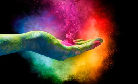 Rainbow colored powder exploding from the palm of a cupped hand © casther - shutterstock