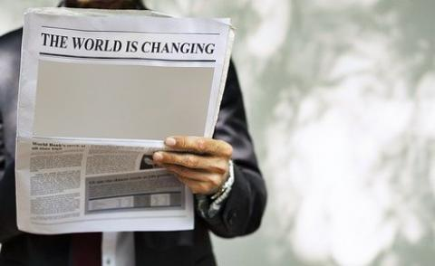 Image of a man holding a newspaper with the headline 'the world is changing'