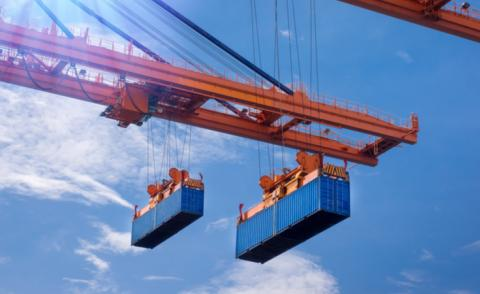 Industrial port cranes lift shipping containers against blue sky © Mr. Amarin Jitnathum - shutterstock