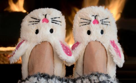 Feet in bunny slippers with open fire behind © Maria Dryfhout - shutterstock