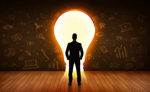 Business man silhouette looks at bright light bulb in wall © ra2 studio - shutterstock